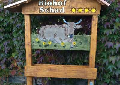 Biohof Schad Werbeschild in Holzgestell mit Dach
