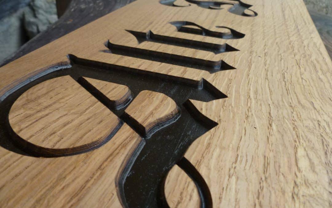 Holzschilder mit vertiefter Schrift in Form geschnitten