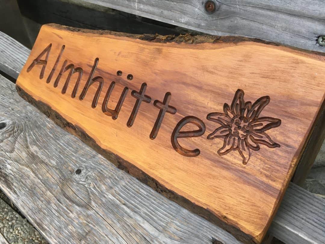 Holzschilder rustikal vertiefte Schrift, Almhütte mit Edelweiß