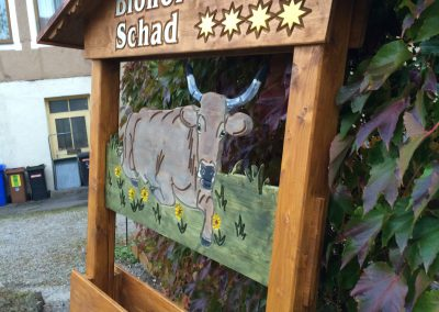 Biohof Schad Holzschild im Balkengestell mit Kupferdach Kuh